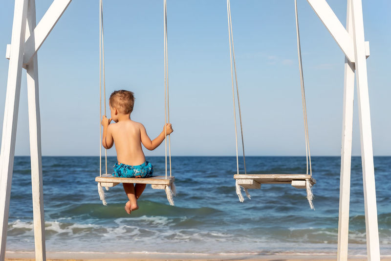 Full length of shirtless boy on sea against sky