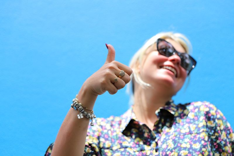 Low angle view of smiling young woman gesturing thumbs up against blue sky