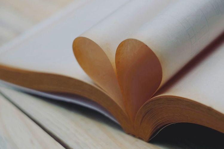 Close-up of heart shape pages in book
