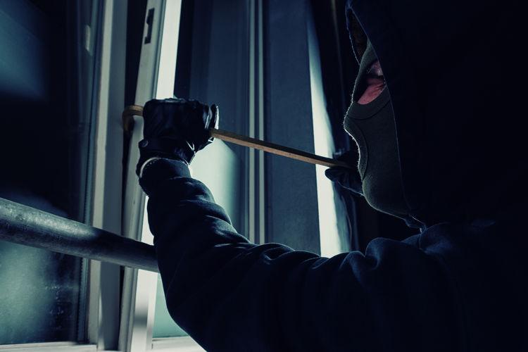 Close-up of burglar breaking window with crowbar
