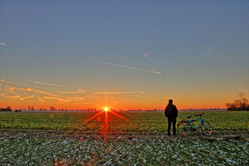 Man with bicycle standing on field against sky during sunset