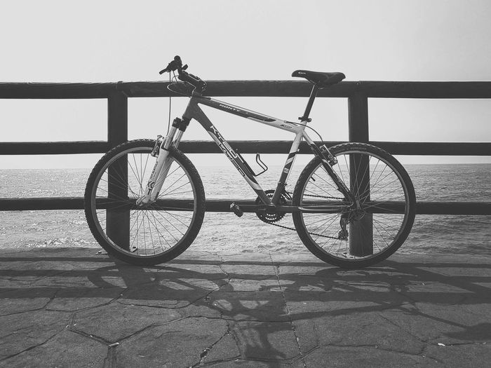 Bicycle parked by railing against sky