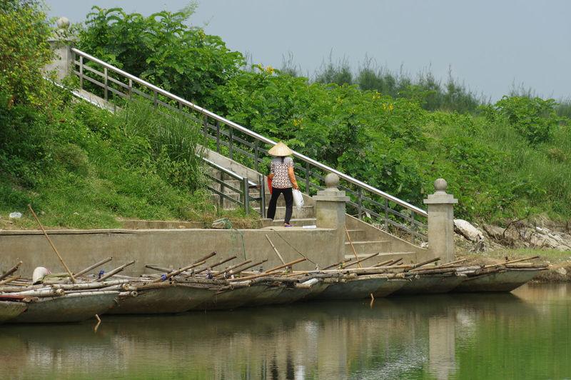 Man standing on footbridge over river against sky