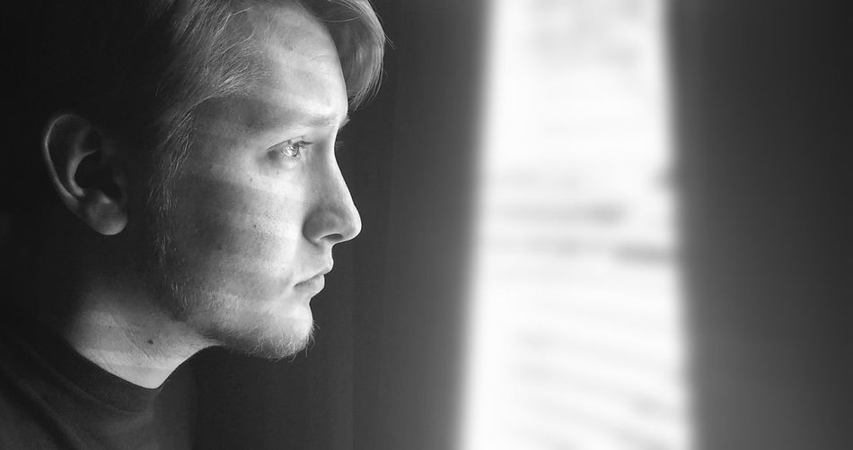 Man Staring out the Window. Black & White Face Portrait Natural Light Portrait