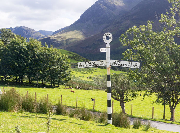 Old road sign or signpost for Buttermere in the English Lake District Lake District Lake District National Park Sign Beauty In Nature Buttermere Buttermere Fell Buttermere Lake Information Landscape Mountain Mountain Range Nature No People Outdoors Road Road Sign Scenics - Nature Sign Signpost Tranquil Scene Tree