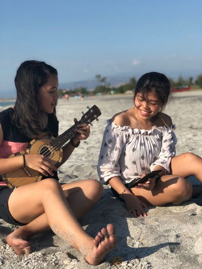 Young woman playing ukulele by friend holding mobile phone while sitting at beach
