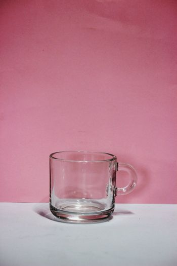 Close-up of empty glass against pink background
