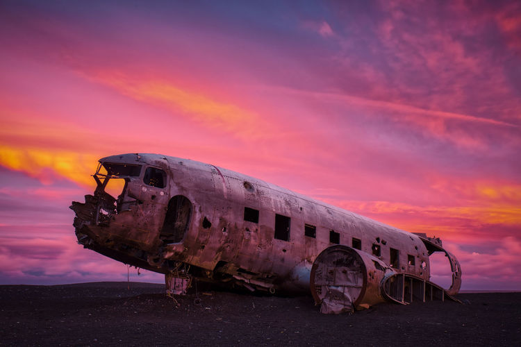 Plane Wreck At Desert Against Cloudy Sky During Sunset