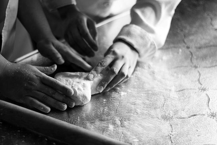 Close-up of hands preparing food on baking sheet