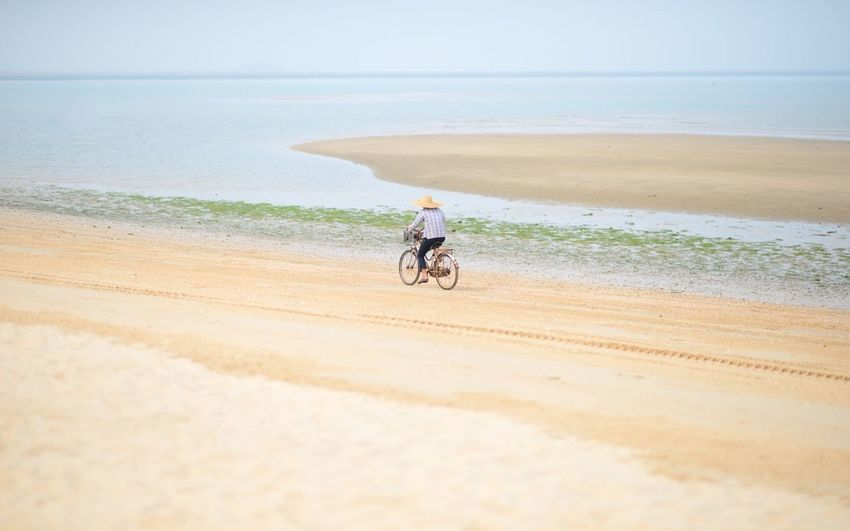 Man cycling on beach