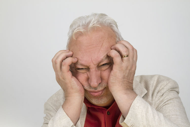 Close-up stressed man making face against white background