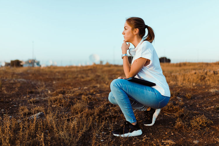 Side view of young woman sitting on land