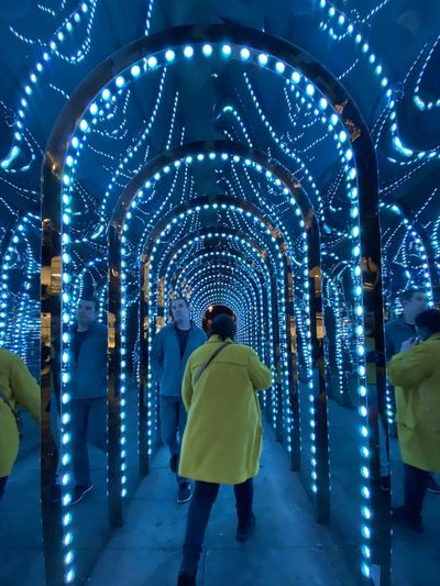 Rear view of people walking in illuminated lights
