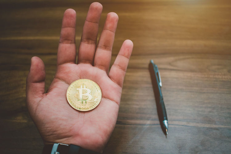 Close-up of hand holding bit coin