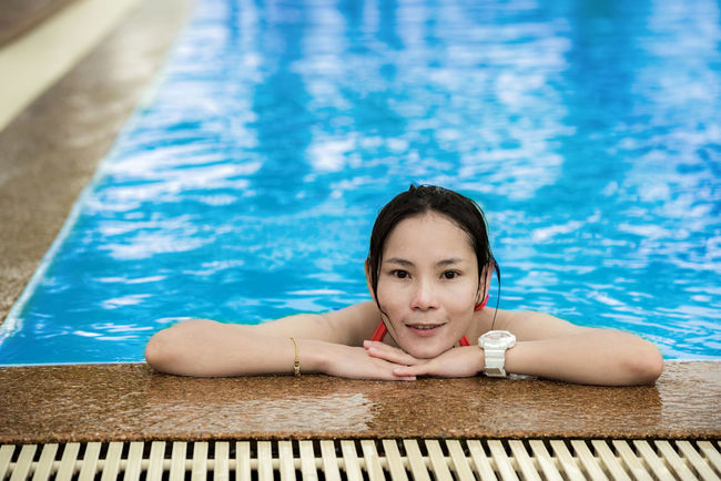 Swimming pool with Asian woman relax and playing pool. Beautiful Woman Blue Day Front View Health Spa Leisure Activity Lifestyles Looking At Camera One Person Outdoors Poolside Portrait Real People Relaxation Spa Spa Treatment Summer Swimming Swimming Pool Swimwear Vacations Water Wood - Material Young Adult Young Women