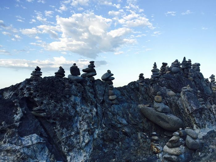 Low angle view of birds perching on rock against sky