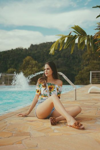 Full length of teenager girl sitting by swimming pool