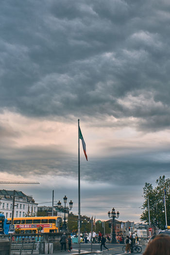 Flag in city against sky during sunset