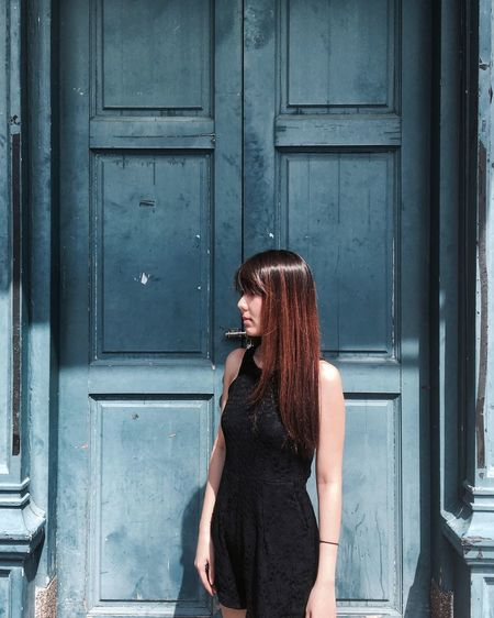 Young woman standing against closed door