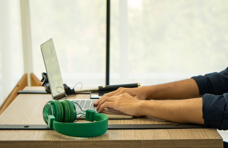 Midsection of man working on laptop on table