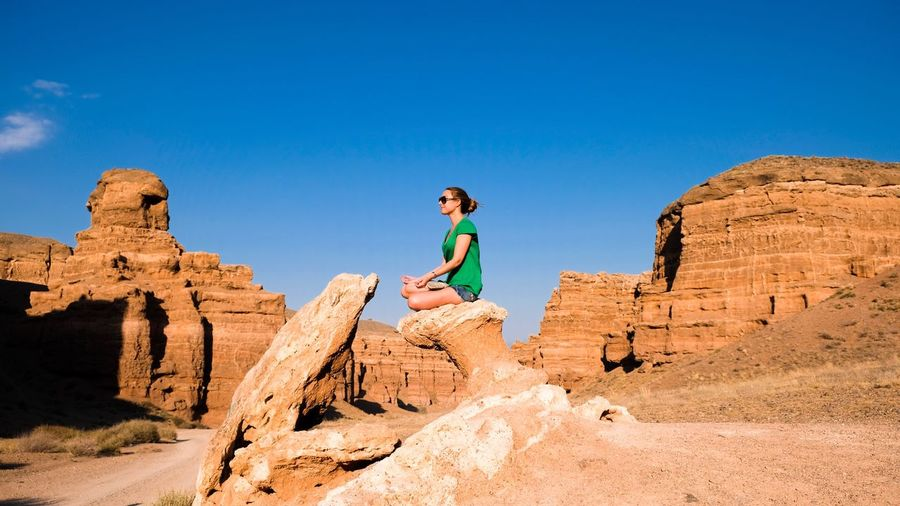 Low Angle View Of Young Woman Sitting On Rock