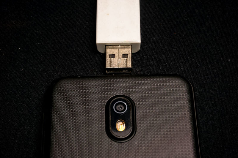 High angle view of mobile phone with usb stick on table