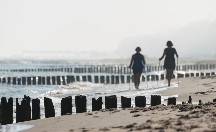 Rear view of women walking at beach against sky