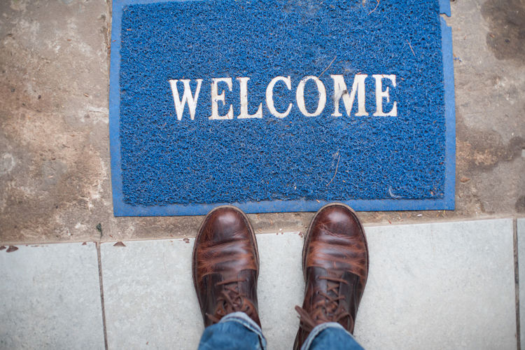 Low section of man standing by welcome text on doormat