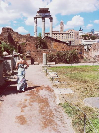 Rear view of woman standing on walkway at roman forum during sunny day