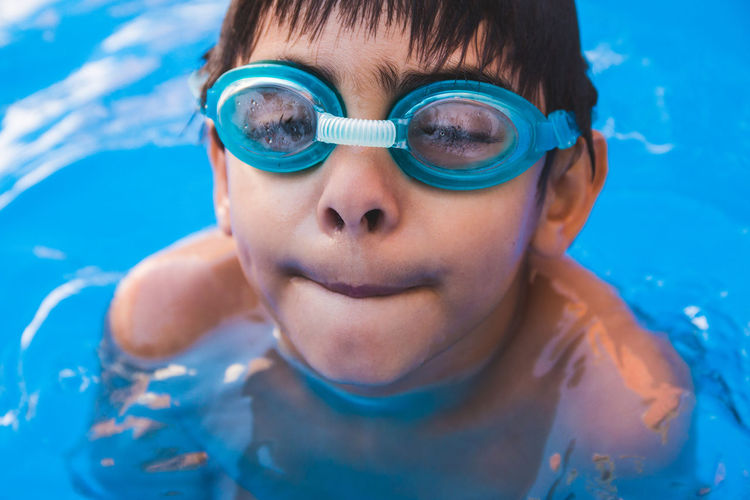 Portrait of cute boy wearing swimming goggles in pool