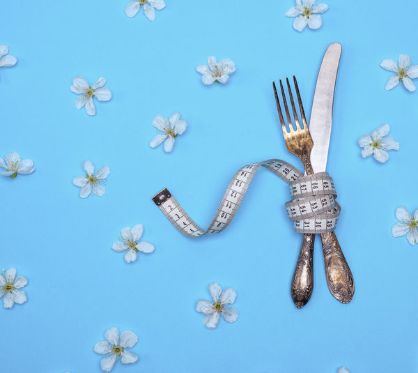 Directly above shot of eating utensils with tape measure amidst flowers on blue background