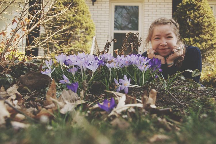 Garden self portrait - girl with crocus in the spring garden Plant Flower Flowering Plant Growth Nature One Person Purple Real People Leisure Activity Lifestyles Day Front View Selective Focus Portrait Mid Adult Young Adult Smiling Outdoors