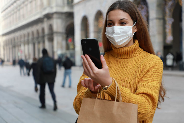 Woman wearing mask video calling on phone standing outdoors