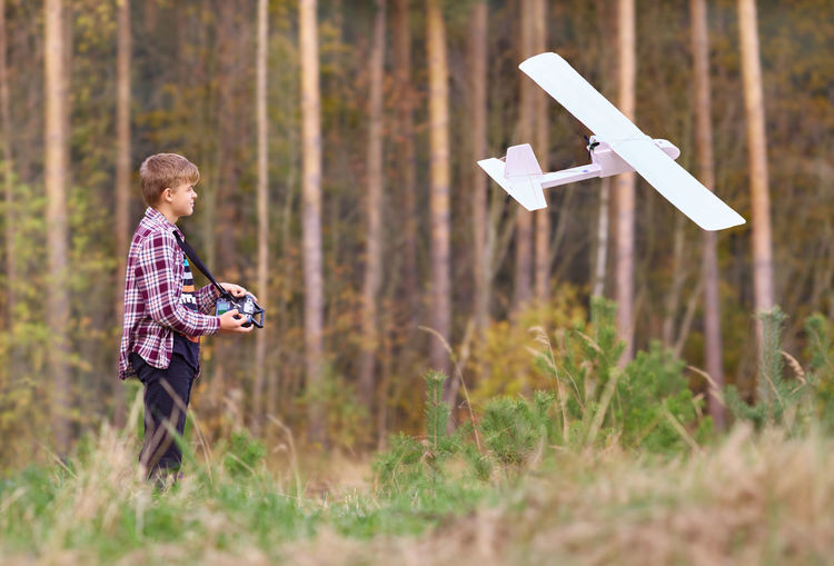 The young man controls a radio-controlled aircraft of his own assembly.