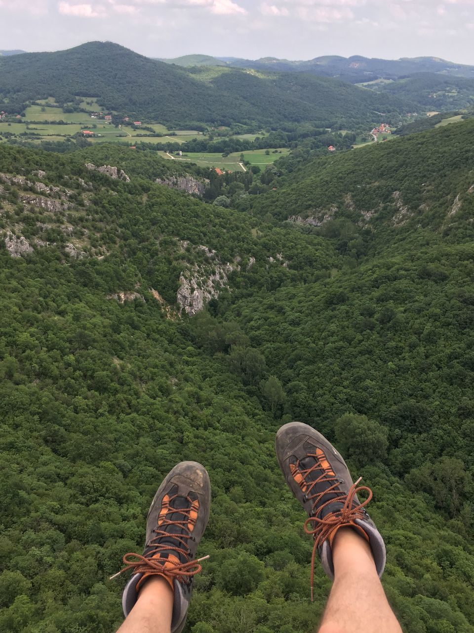 shoe, mountain, low section, real people, human leg, one person, personal perspective, green color, standing, day, nature, men, high angle view, outdoors, hiking, beauty in nature, human body part, lifestyles, landscape, mountain range, grass, one man only, close-up, sky, people