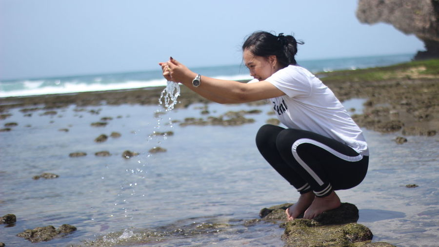 Side view of woman playing with water at beach