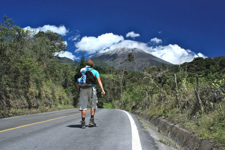 Rear View Of Hiker Walking On Road Against Sky