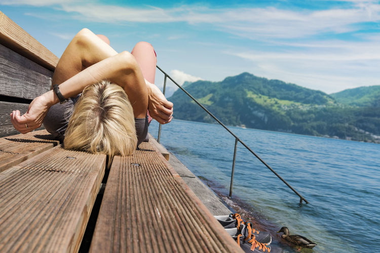 Woman lying down at lake against sky