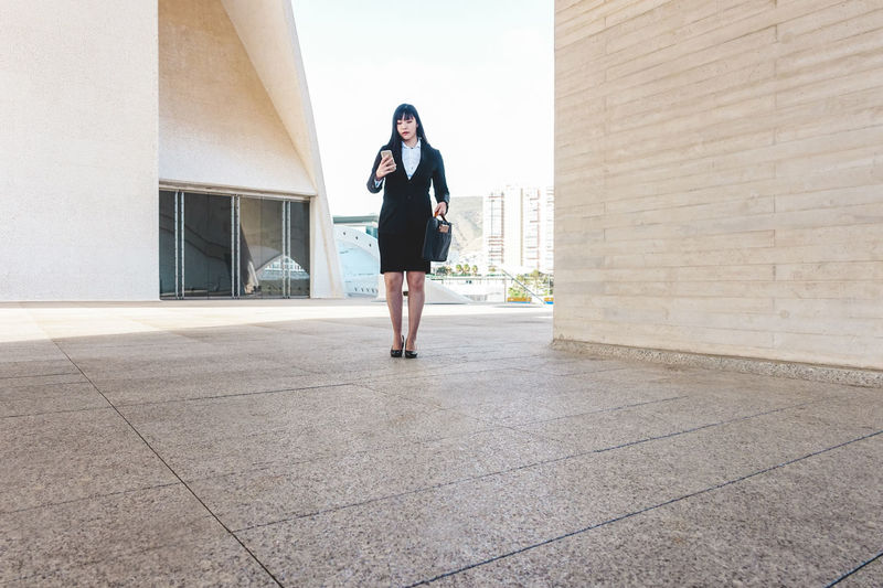 Full length of young woman standing against building