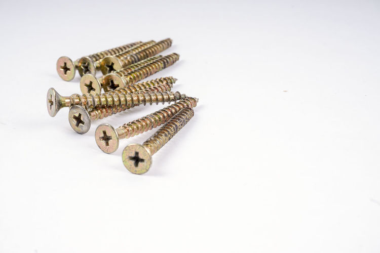 SCREWS ISOLATED ON WHITE Bolts And Screws Construction Close-up Copper  Indoors  Metal Metal Industry No People Nut Screw Sharp Studio Shot White Background