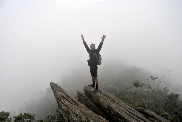 Man with arms outstretched standing on mountain