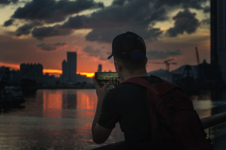 Rear View Of Man Photographing Sunset Over City At Kowloon Bay