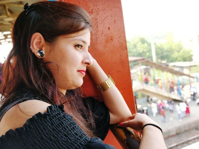 Side View Of Thoughtful Young Woman Looking Away On Bridge