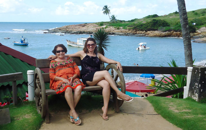 Full length of happy women sitting on bench against sea