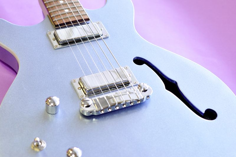 High angle view of blue guitar on purple background