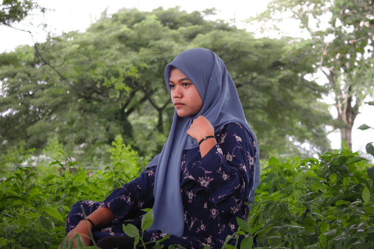 Young woman looking away while standing on land against trees