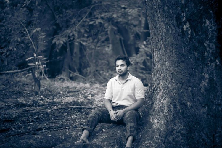 Thoughtful Man Sitting On Tree Root At Forest