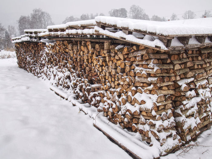 Chopped stock of firewood under snow, regular pile from cut wood