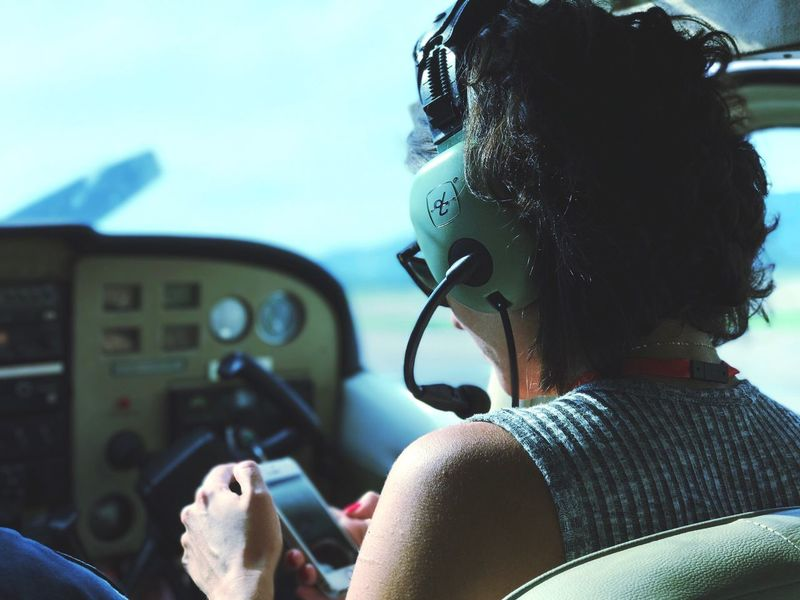 Woman pilot checking iPhone Real People Headshot Transportation One Person Vehicle Interior Mode Of Transport Day Side View Head And Shoulders Analogue Lifestyles Leisure Activity Young Adult Close-up Outdoors Sky Headset Young Women Cessna172 Airplane IPhone Digital Vehicle Seat Desktop Background Wallpaper