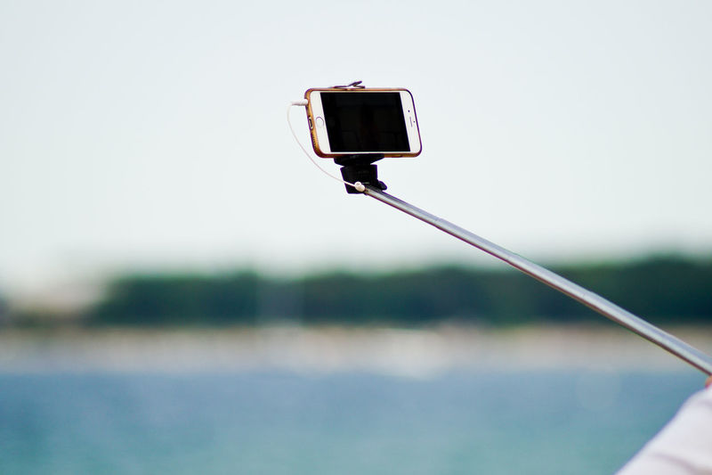 Close-up of mobile phone on selfie stick